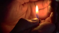 A lighter in the dark - hand cupped to protect flame Stock Footage
