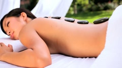 Asian Girl Relaxing with Hot Stone Massage Stock Footage