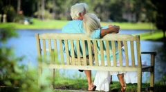 Retired Couple Sitting Outdoors on Park Bench Stock Footage