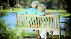 Happy Senior Couple Relaxing on Park Bench Stock Footage
