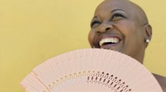 Mature african woman with fan, smiling Stock Footage
