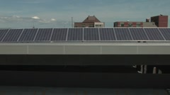 Boom up on solar panles in city setting Stock Footage