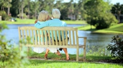 Affectionate Senior Couple Relaxing on a Park Bench - stock footage