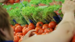 Girl arranges vegetables at the supermarket Stock Footage