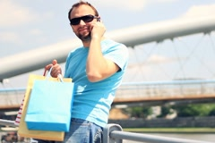 Man with shopping bags on the bridge talking on mobile phone Stock Footage