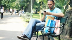 Man with shopping bags sending sms, texting in the park - stock footage