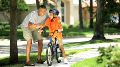 Young Ethnic Father Encouraging Son on Bicycle - stock footage