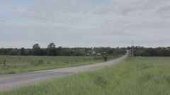 Amish traveling in horse and buggy. - stock footage