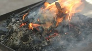Stock Video Footage of Blacksmith turning bronze already charred coffee maker on live coals