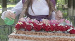 Young woman holding rose bouquet on tray, spraying, adjusting them Stock Footage