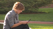 Business woman texting on cell phone at park Stock Footage