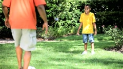 Ethnic Father & Son Kicking a Ball Together Stock Footage