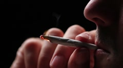 Man lighting a joint, close up on black - stock footage
