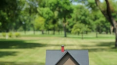Hand lifting model house into empty lot Stock Footage