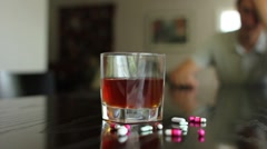 Substance abuse, pan shot of pills and alcohol out of focus man in background - stock footage
