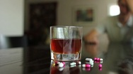 Substance abuse, pan shot of pills and alcohol out of focus man in background Stock Footage