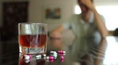 Substance abuse, pills and alcohol out of focus man in background - stock footage