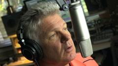 MAN TALKS INTO MICROPHONE Stock Footage