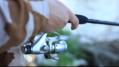 Close up of man's hands reeling in a fishing pole - stock footage