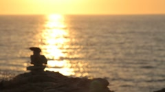 Stack of zen stones with sunset over sea in background Stock Footage