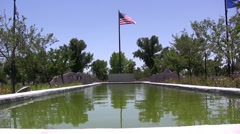 Beautiful american flag in front of pond fountain Stock Footage