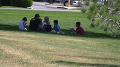 Family eating lunch together in the shade at the park - stock footage