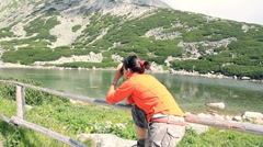 Attractive woman taking photos in the mountains by the lake, steadicam shot Stock Footage