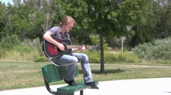 Playing the guitar on a park bench - stock footage
