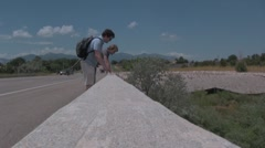 Two guys throwing rocks off the bridge Stock Footage
