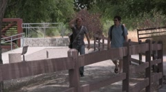 two kids walking along the fence line road - stock footage