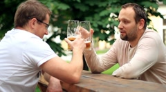 Two male friends talking and drinking beer, outdoors Stock Footage