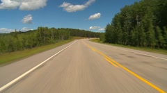 Drive plate, forested hilly rural, distant following traffic, mostly sunny Stock Footage