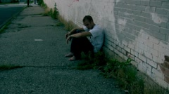 Gryngy kid against a brick wall in the ghetto homeless Stock Footage