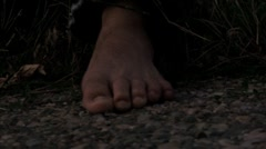 Homeless mans toes and feet in the gravel cringing Stock Footage