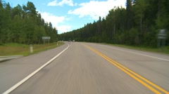 Drive plate, forested hilly rural jeep follows in distance, mostly sunny, #1 Stock Footage