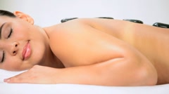 Brunette Spa Client Relaxing with Hot Stone Therapy Stock Footage