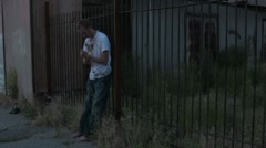 Poor Homeless Man Agaings a fence in a dark ally - stock footage