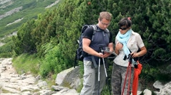 Young couple of hikers with compass looking at a map in the mountains Stock Footage