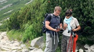 Stock Video Footage of Young couple of hikers with compass looking at a map in the mountains