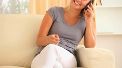Woma sitting on a sofa calling a friend Stock Footage