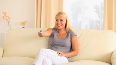 Woman sitting on a sofa with a remote Stock Footage
