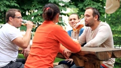 Four friends drinking beer, outdoors Stock Footage