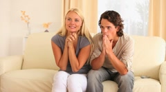 Excited couple sitting on a sofa - stock footage