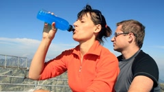 Female hiker drinking isotonic drink in the mountains, steadicam shot Stock Footage