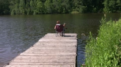Elderly woman fishing from the dock. Stock Footage