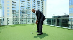 Ethnic Businessman Practicing Golf on City Office Roof Stock Footage