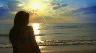Girl sitting near Sea at Sunset Stock Footage