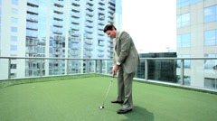 Young Businessman Practicing Golf on Office Rooftop - stock footage
