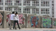 Chinese couple walk past graffiti on campus, love at China university Stock Footage