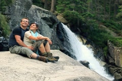 Happy couple relaxing by the beautiful waterfall, slow motion NTSC Stock Footage
